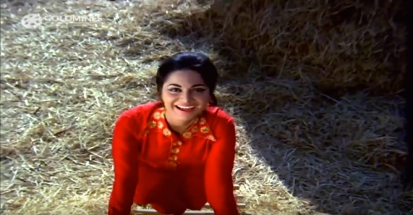 Waheeda climbs up a haystack